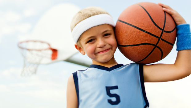 A child wearing a blue basketball tee with the number 5 on it. He has a white headband on. He is carrying a basketball next to his face/