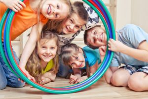 A group of children took their faces through a hula hoop and smile at the camera