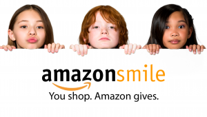 A group of three children holding a sign that says amazon smiles