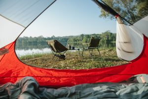 Look from inside of an open tent. Two foldable chairs are visible. A lake is in the background.