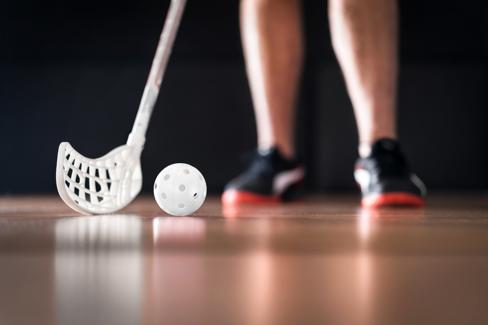 An out of focus pair of feet shown below the knee. They are wearing a pair of black tennis shoes. In focus is a white floor hockey stick. next to it is a white hockey ball.