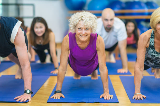 A woman in a yoga class smiles at the camera. Everyone is on yoga mats. They are in a pushup position.