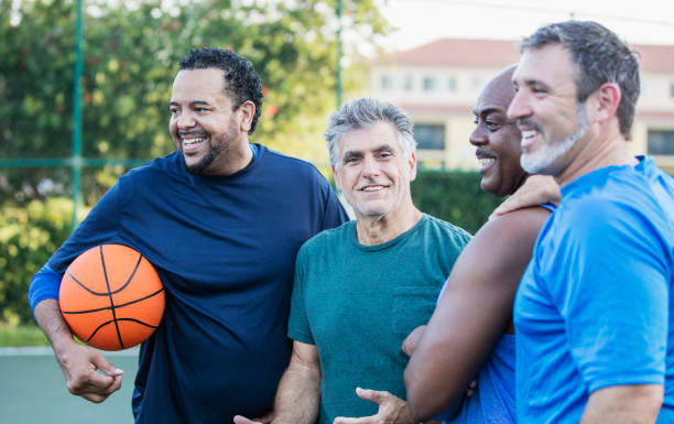 A multi-ethnic group of middle-aged and senior men on an outdoor basketball court. The Caucasian man wearing the green shirt, looking at the camera, is a senior, in his 60s. The bald African-American man is in his 50s, and their friends are mature men in their 40s.