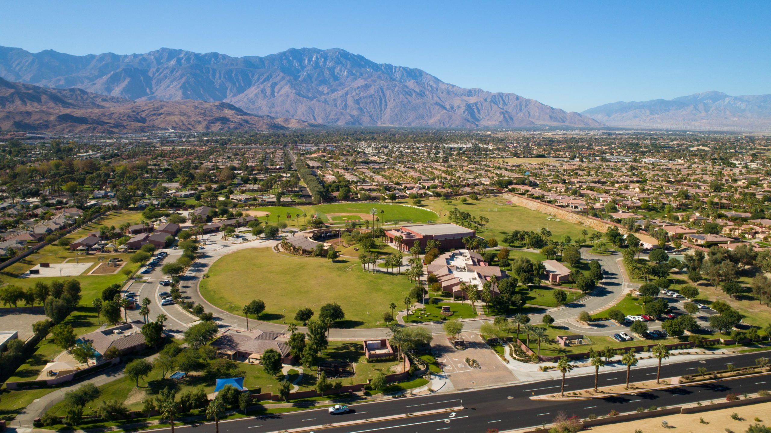 aerial photo of palm valley school. It is surrounded by mountains and clear blue skies.