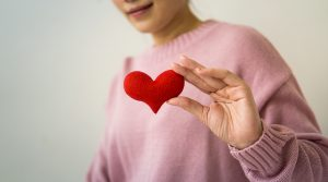 A woman with a pink long sleeved sweater is holding a red 3d heart to the camera.