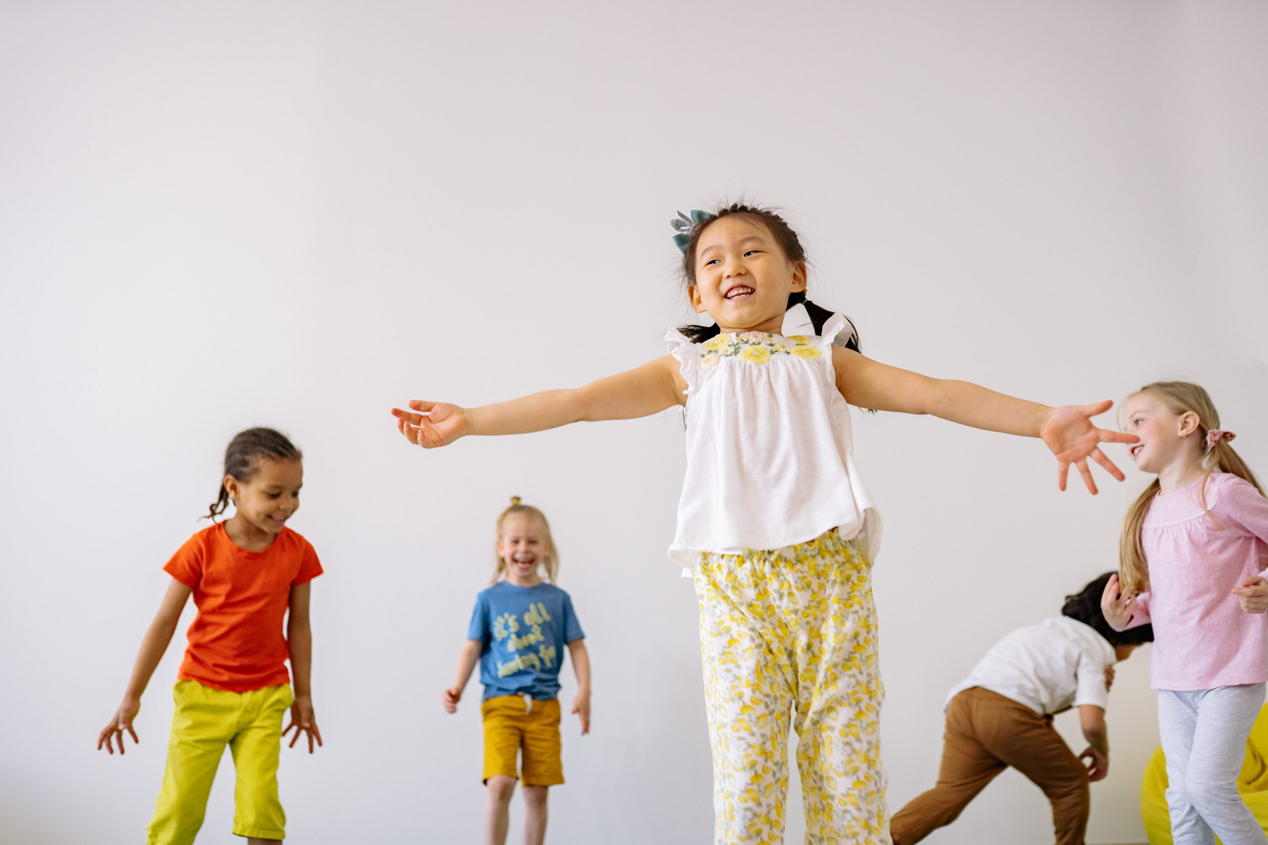 A group of five children jumping and dancing. Behind them is a white backdrop. The girl in the center is wearinga. white shirt and light yellow pants. The girl on the left is wearing a red shirt and mustard yellow pants. Next to her a girl is wearing a blue shirt and dark yellow shorts. Next to her a girl is crouched. She is wearing a white long sleeve shirt and brown bands. Next to her is a girl wearing a pink long sleeve shirt and. light blue leggings. Family YMCA of the Desert Dance page.